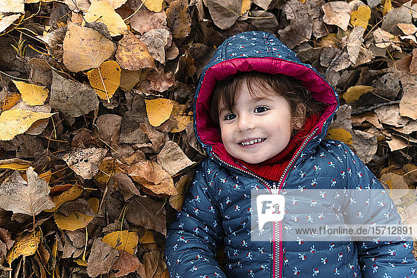 Portrait of happy little girl lying on autumn leaves