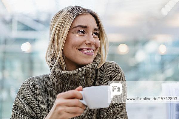 Porträt einer lächelnden jungen Frau  die eine Tasse Kaffee hält und wegschaut