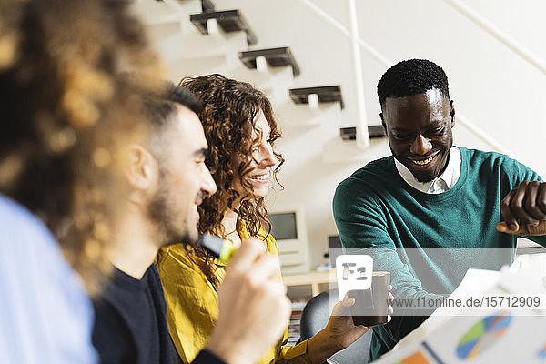 Lächelnde Kollegen bei einer Besprechung im Büro