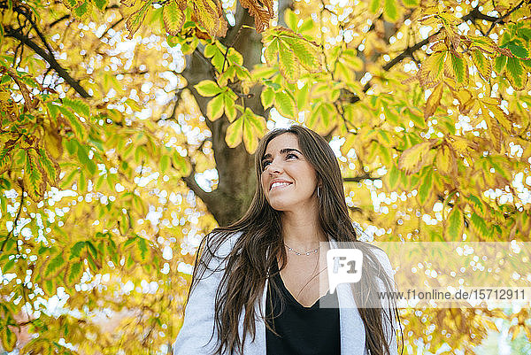 Smiling woman standing under autumnal tree