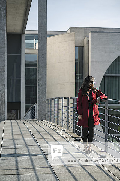 Modern businesswoman standing on a bridge and looking sideways  Berlin  Germany
