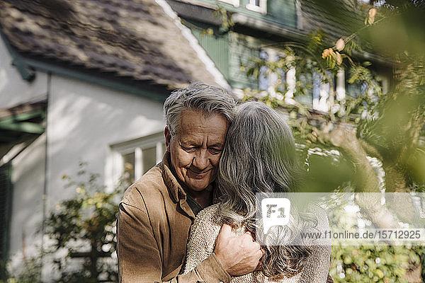 Älterer Mann umarmt seine Frau im Herbst im Garten ihres Hauses