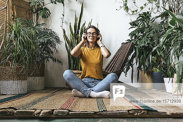 Entspannte junge Frau sitzt zu Hause auf dem Boden und hört Musik