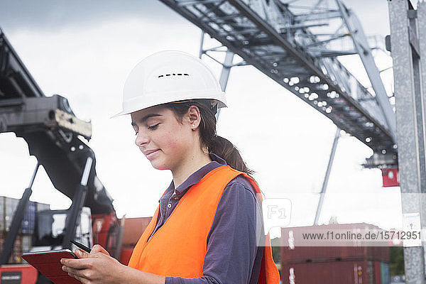 Female worker with clipboard taking notes on industrial site