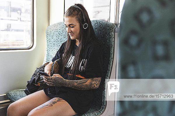 Tätowierte junge Frau sitzt mit Smartphone und Kopfhörern in der Pendlerschlange  Berlin  Deutschland