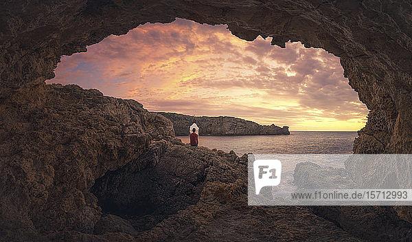 Rückansicht eines Menschen  der bei Sonnenuntergang in einer Höhle sitzt  Menorca  Spanien