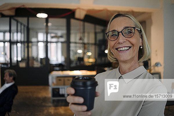 Porträt einer glücklichen reifen Geschäftsfrau bei einer Kaffeepause im Büro