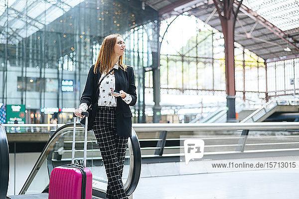 Junge Frau mit Koffer und Handy am Bahnhof