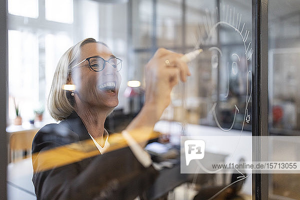 Happy mature businesswoman drawing face on glass pane in office