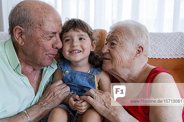 Glückliche Großeltern mit kleinem Mädchen zu Hause