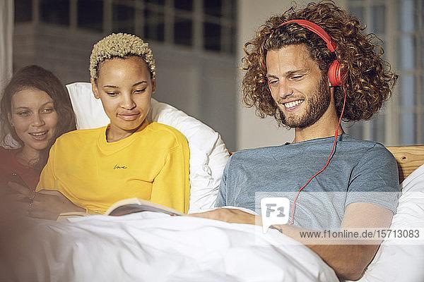Glückliche Freunde entspannen zu Hause im Bett