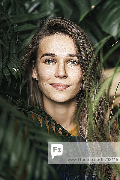 Portrait of a young woman amidst green plants