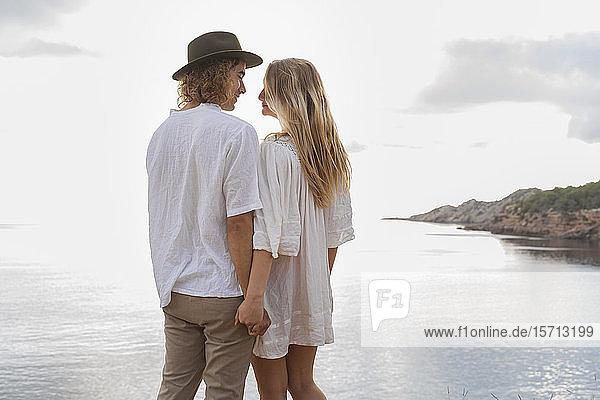 Verliebtes junges Paar  das vor dem Meer steht und Händchen hält  Ibiza  Balearen  Spanien