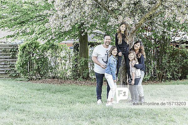Glückliche Eltern mit drei Drillingsschwestern auf der Wiese