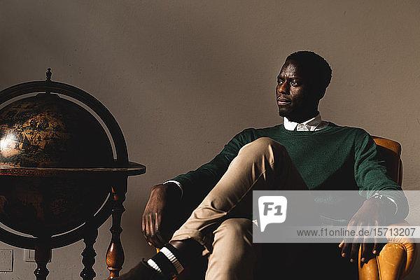 Mann sitzt in Ledersessel neben antikem Globus und schaut zur Seite