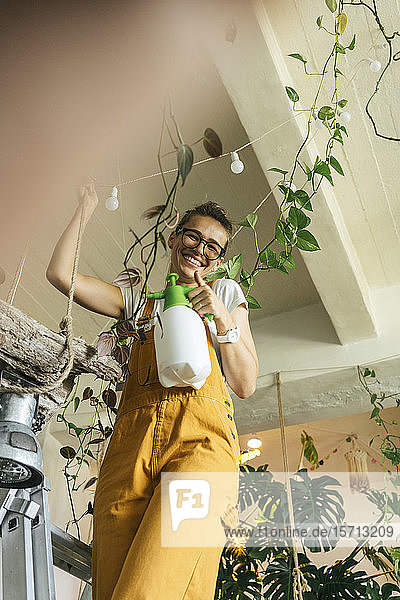 Happy young woman standing on a ladder caring for plants in a small shop