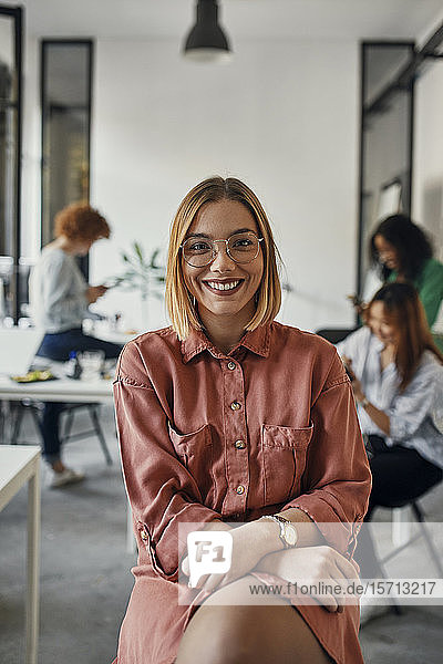 Portrait of a confident businesswoman in office with colleagues in background