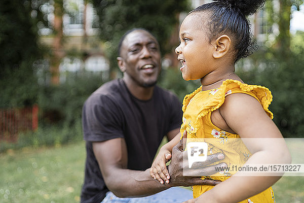 Father holding his daughter in a park