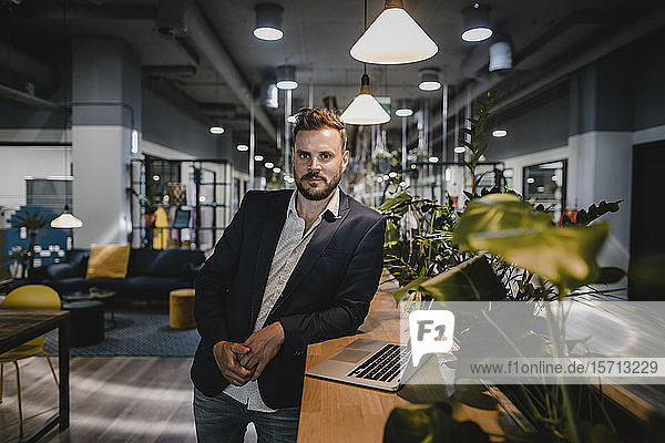 Businessman with laptop in coworking space