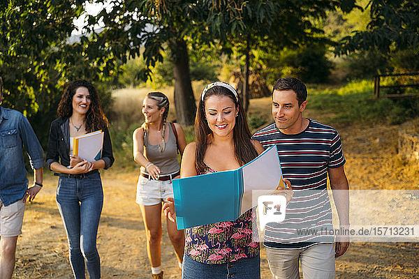 Freunde auf Exkursion mit Folder in ländlicher Landschaft