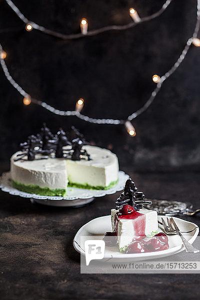 Stück Käsekuchen ohne Backen,  dekoriert mit Schokoladen-Weihnachtsbäumen auf Teller mit heißer Kirschsauce