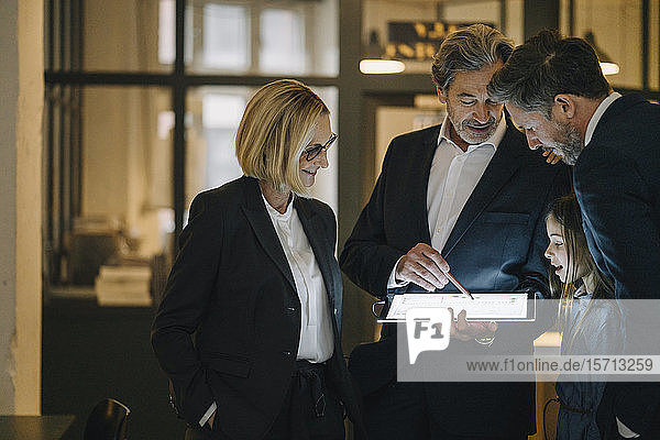 Business people and girl looking at shining tablet in office