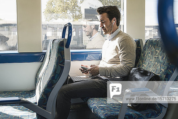 Young man with earphones using smartphone and tablet on a train