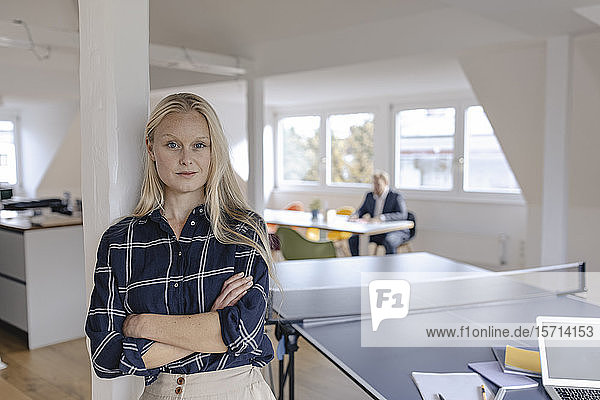 Portrait of young businesswoman in office with table tennis table