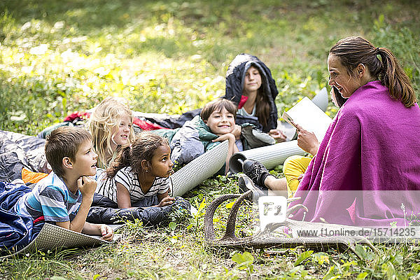Teacher reading story to school children  camping in the forest
