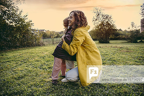 Happy mother and daughter hugging on a meadow in autumn