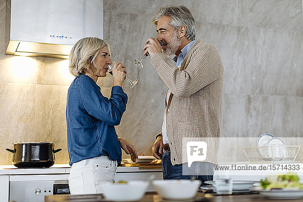 Mature couple drinking red wine in kitchen at home