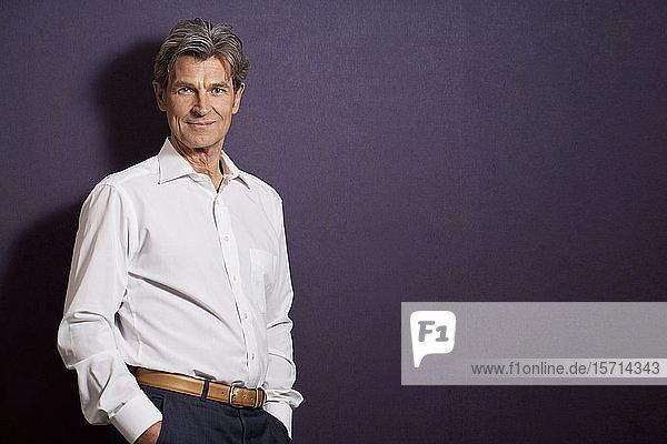 Porträt eines selbstbewussten Geschäftsmannes vor einer violetten Wand