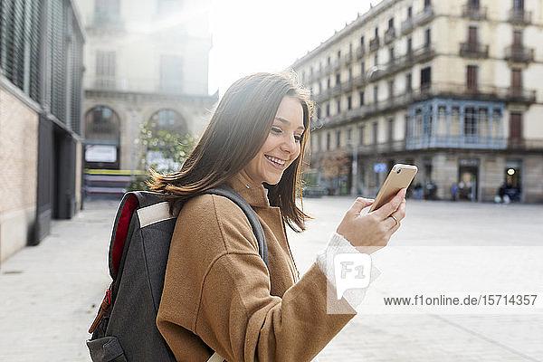 Glückliche junge Frau mit Mobiltelefon in der Stadt  Barcelona  Spanien