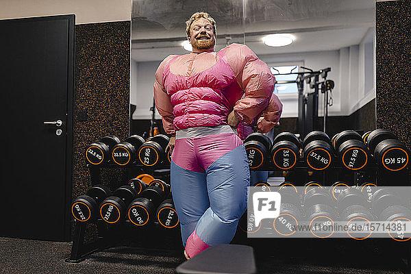 Proud man wearing pink bodybuilder costume in gym