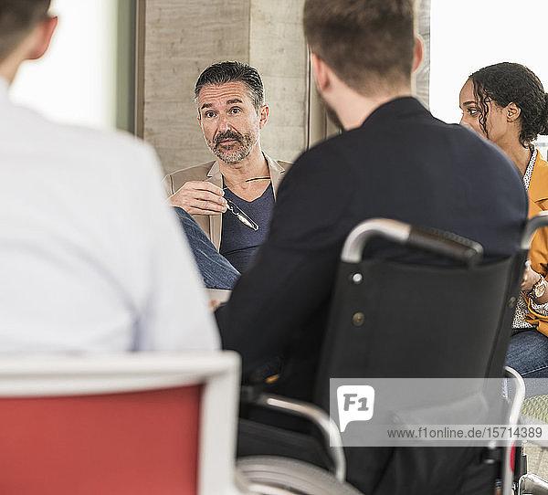 Geschäftsleute  die eine Besprechung im Büro haben  bei der einer im Rollstuhl sitzt