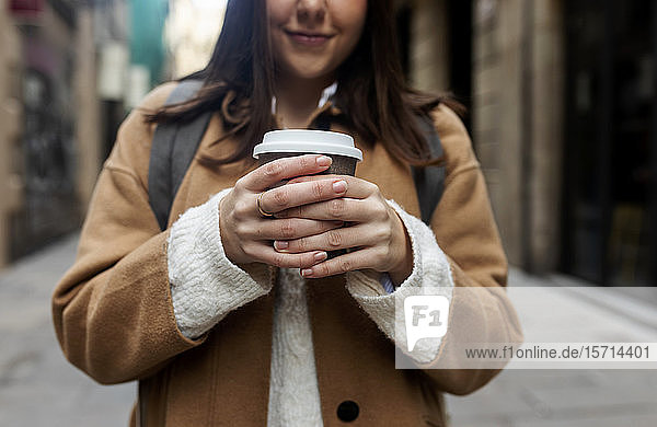 Close-up of young woman with takeaway coffee in the city  Barcelona  Spain