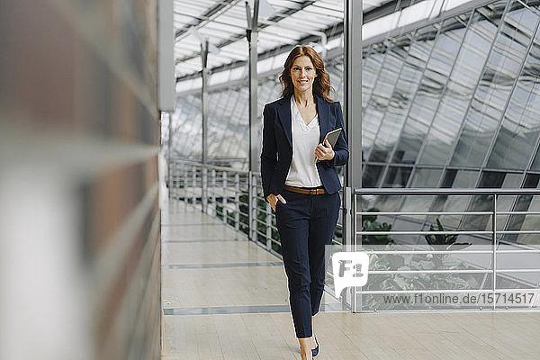Selbstbewusste Geschäftsfrau hält ein Tablett in einem modernen Bürogebäude