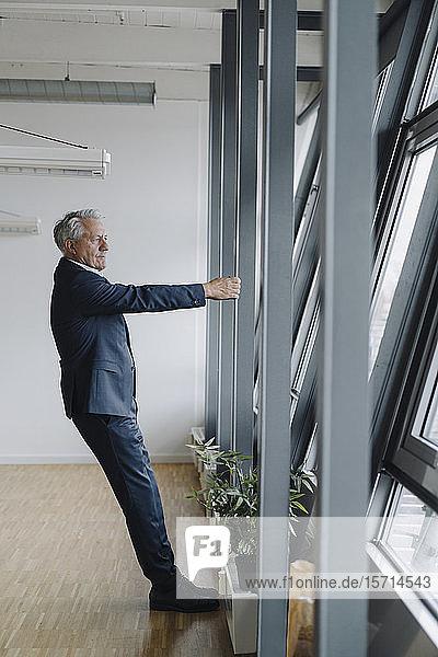 Leitender Geschäftsmann mit Träger im Amt