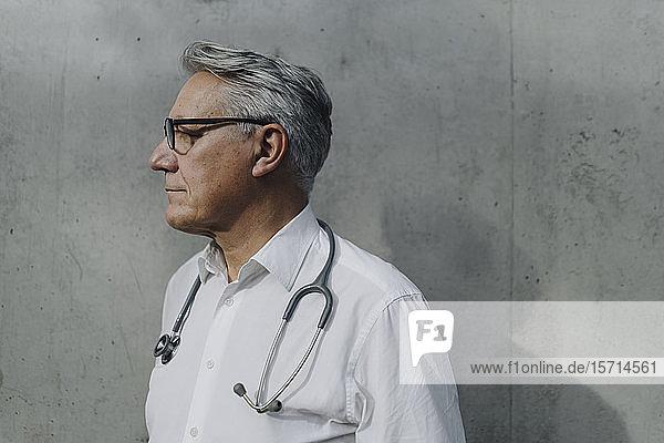 Nachdenklicher Oberarzt an einer Betonwand