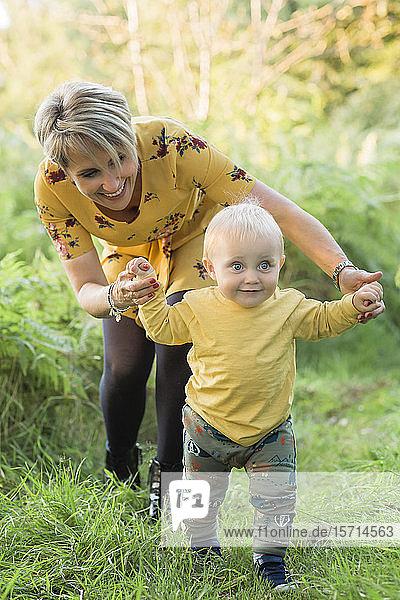 Mutter hilft kleinem Sohn beim Spaziergang auf einer Wiese