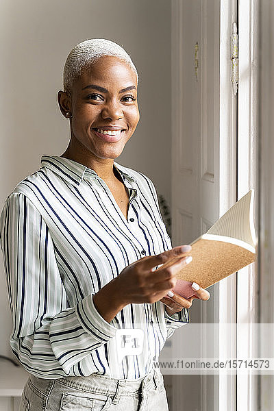 Portrait of smiling woman with notebook at the window