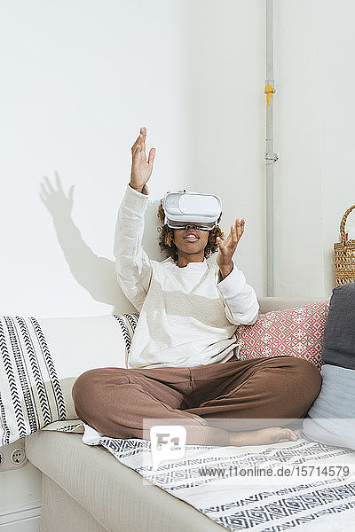 Young woman at home wearing VR glasses