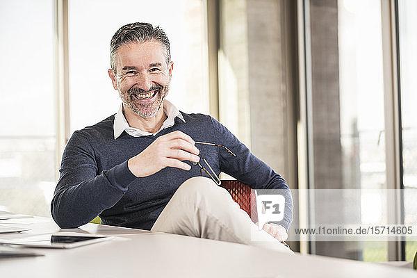 Porträt eines glücklichen reifen Geschäftsmannes  der im Büro am Schreibtisch sitzt
