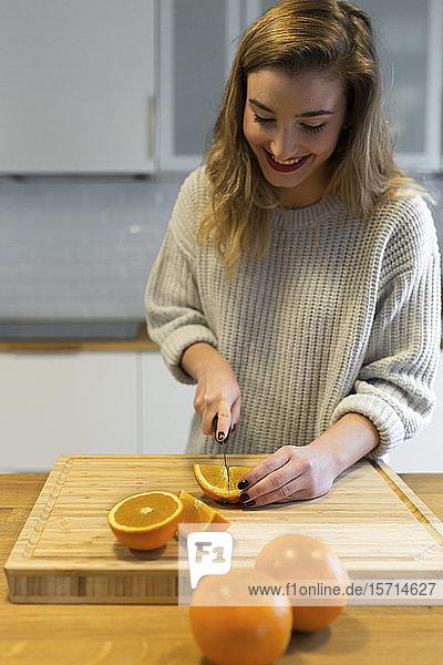 Weiblicher Teenager beim Orangenschneiden in der Küche