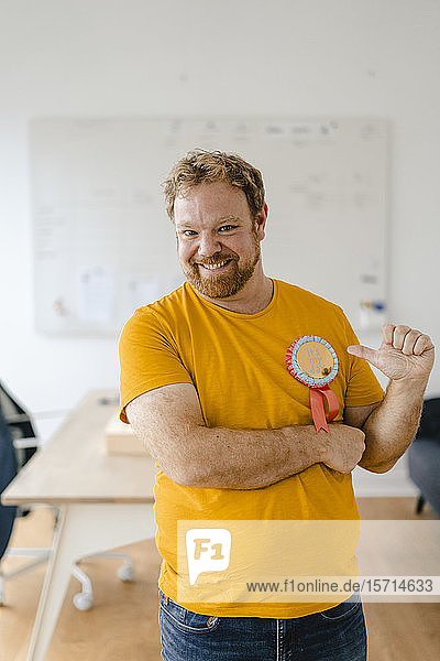 Portrait of a happy casual businessman with an award in office
