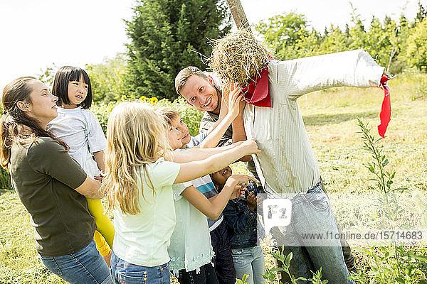 Schulkinder auf einem Ausflug mit einer Vogelscheuche auf einem Feld