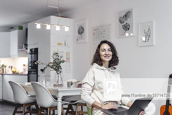 Porträt einer lächelnden Frau mit Laptop zu Hause