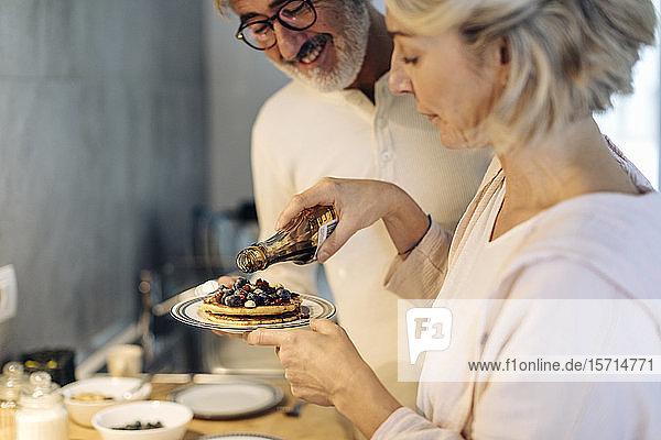 Reifes Paar bereitet zu Hause in der Küche Pfannkuchen zu
