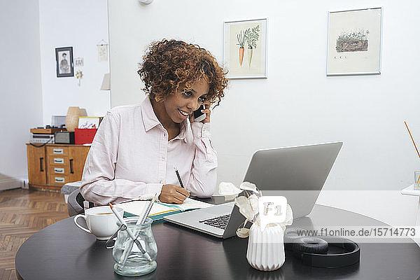 Junge Frau  die zu Hause arbeitet und telefoniert