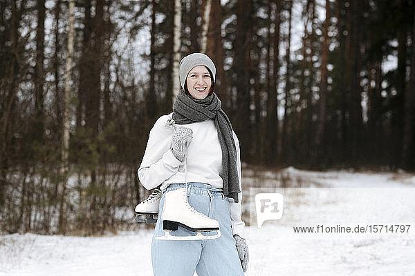 Porträt einer glücklichen Frau mit Schlittschuhen im Winter
